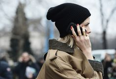 Spring look idea: a transitional jacket, toque, red nails, and a TON of gold rings (shot by Tommy Ton)