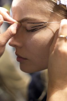 En backstage du défilé Anthony Vaccarello automne-hiver 2014-2015 | Use string to make straight lines for graphic makeup.