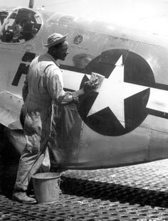 """""""Staff Sgt. William Accoo..., crew chief in a Negro group of the 15th U.S. Air Force, washes down the P-51 Mustang fighter plane of his pilot with soap and water before waxing it to give it more speed."""" Ca. September 1944."""