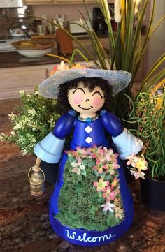 This Beautiful Lady is made of clay Pots. She is Painted and finished, the decorated with a watering can, flowers, necklace, and straw hat. Her blue dress has a welcome sign painted on the bottom hem.