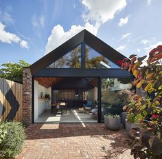 Black anodized aluminum cladding frames the window wall that separates the main living space from the back garden. The garden's paving was done with recycled red brick and the chevron pattern on the fence echoes the motif on the living room wall.