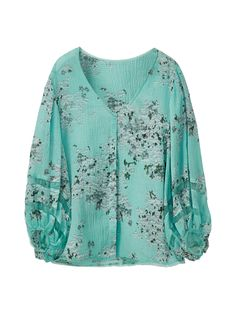 Camisa con estampado floral, confeccionada en tejido de algodón y seda morera. Corte recto, cuello pico, cierre mediante botonadura oculta por tapeta y manga 7/8 abullonada.