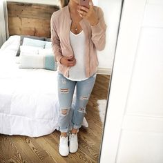 Blush pink bomber jacket over white tee, light wash ripped jeans and white sneakers
