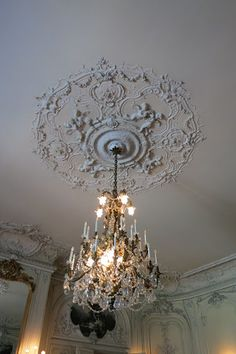 The ballroom is adorned with elaborate white stucco relief decorations.  The ceiling medallion features winged cherubs and the Baccarat crys...