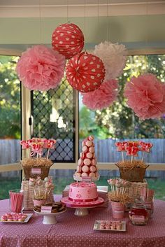 Tissue pom poms hung over candy buffet