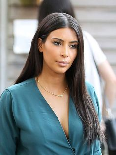 Centered parted straight hairstyle from the famous kim Kardashian that always rocks this style with her dark hair.