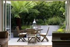 Small town garden with patio with raised beds, tree fern and table and chairs.