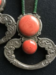 A pair of large belt pendants, each composes a roundel and a ring inset with cabochon coral, suspended on a leather loop. 19th c Mongolia. Private collection