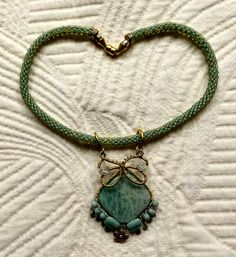 Wire-wrapped Sterling Silver over Amazonite large bead; Eni Oken style. Brick Stitch beaded neckpiece with magnetic clasp and Bali ss beads and charms.