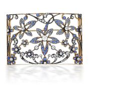 A sapphire and diamond 'plaque de cou' The slightly curved openwork rectangular plaque, decorated with three flowerheads surrounded by scrolling floral and foliate decoration, set throughout with circular-cut sapphires and old brilliant-cut diamonds.