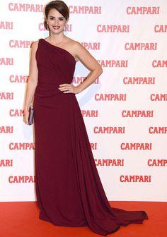 Para la presentación del calendario Campari, del cuál es imagen, Penélope Cruz eligió un vestido burdeos asimétrico, drapeado y con ligera cola muy favorecedor.