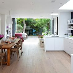 Open plan kitchen. White kitchen, white work surface. Wooden table and floor.