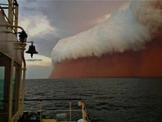 Australia's Surreal Red Wave - Jan 9 2013  - brewing thunderstorm moved reddish colored sand and dust over the Indian Ocean.  Brett Martin