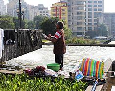 Moradora de rua lava suas roupas em fonte na na Praça Sé