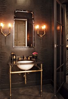 In the powder room, the faux-crocodile wall covering is by Osborne & Little; the fixtures are by Waterworks.