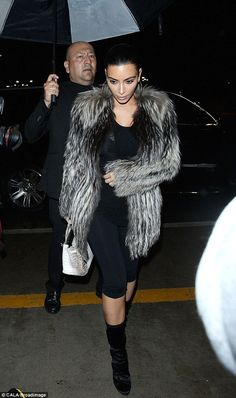 Glamorous arrival: A bodyguard held an umbrella over Kim to keep her dry in the rain as she dashed into the airport