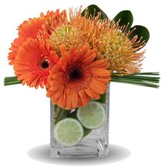 Citrus Splash. Lime greens and zesty oranges compose a design that is truly refreshing. Gerber daisies, pincushion protea, limes www.drdelphinium.com