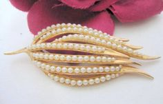 Offered by VintagObsessions, this lovely faux pearl brooch is made up of all  faux pearls set in gol