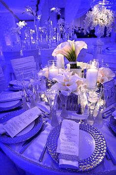 Use of blue lighting within a white wedding. Several different types of floral arrangements were used to accomplish this look: mixed smaller arrangements, tall glass cylinders with sprays of orchids, and opulent display pieces perched on top of pedestals