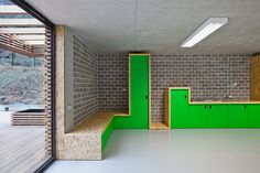 Metaform Architects // Albergue en Larochette // osb cabinets along the wall with green doors