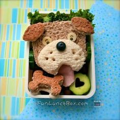 """Lunch #109 - """"Doggy sandwich"""". use up the end pieces of the brown bread, turkey sandwich. Added some grapes, and cucumber. The bone is made using strawberry jam, and formed some ham into a tongue. Artist got inspiration from bentofun."""
