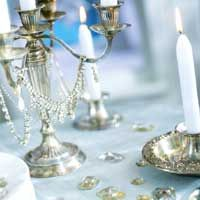 For a romantic, dressy table -- perhaps a New Year's Eve dinner for two or four -- layer on the rhinestone jewelry: Drape a silver candelabra with necklaces and earrings and scatter large rhinestones (or crafts-store look-alikes) around the table to catch the light.