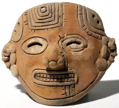 La Tolita, Ecuador, c. 500 BC - 300 AD. Superb terracotta maskette! Deeply incised with a variety of intricate designs. The individual is lavishly adorned with multiple nose ornaments and complex ear ornaments.