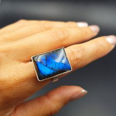 This large cobalt blue beautiful labradorite ring will take your breath away! Wear this magical flashy crystal as an everyday statement piece that goes with any wardrobe style. This labradorite ring features a rectangular shape, shimmering shades of blue and a modern design.  I love wearing labradorite rings for empathic protection. Wear this ring to protect your aura when youre out running errands, going to work or attending events with lots of people. If youre a lover of labradorite…