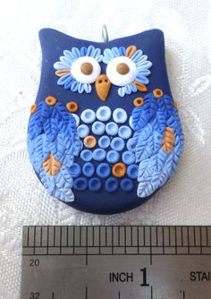 Polymer clay Owl pendant, handmade with applique technique, one of a kind. Dark blue with wings and feathers in gradient from blue to baby blue with touches of various shades of bronze and dark bronze eyes. By Lis Shteindel.