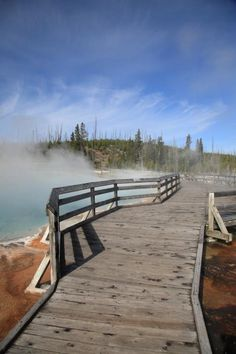 Yellowstone Park - West Thumb Geyser Basin. Wooden bridge through steaming geothermal geyser on the shore of Yellowstone Lake. Appears to be a dangerous crossing over a fiery landscape, but the bridge actually overlooks a pretty hot spring.