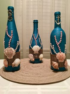 : This bottle is hand wrapped in teal thread and then decorated with real sea shells, faux pearls, mesh and metal emblem. It is perfect for any beach fanatic and sea lover, bringing the feel of the ocean into your home. **MADE IN AMERICA** Every bottle or Glass Bottle Crafts, Wine Bottle Art, Painted Wine Bottles, Recycled Wine Bottles, Diy Bottle, Glass Bottles, Vodka Bottle, Empty Bottles, Altered Bottles