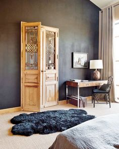 Wood door with wrought iron details on windowpanes, faux fur charcoal rug, and small wood desk