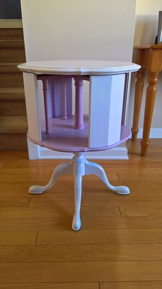 A simple and sweet addition to any room!  This vintage table was given a make-over with a coat of white paint with a pink-painted interior.  The lower level spins! Perfect for storing liquor bottles and craft supplies.  Made of wood, this piece has four windows into the lower level. Each window measures about 7.75 x 10.5. The table top measures about 20 inches in diameter. In total, the table measures about 26 inches tall.  Vintage pieces are not perfect and have their own personalities…