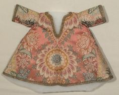 A child's (bambino) brocade dress, 1732-1819. A large centrally placed flower on rose ground draws the eye. Information supplied by #Snowshill notes: It is unlined but the hem and the sleeves are faced with apricot silk. Neck opening and hem edge trimmed with gilt lace. The fabric is French (transitional 1720s-1730s) with garment constructed early 18thc. Ecclesiastical costume (?) From www.NationalTrustCollections.org.uk