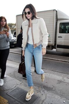 While off-duty during Paris Fashion Week, Jenner goes for a casual look in a bomber jacket,RE/DONE | Levi's high-rise jeans, Stella McCartney platform brogues, and a Kurt Geiger London tote.