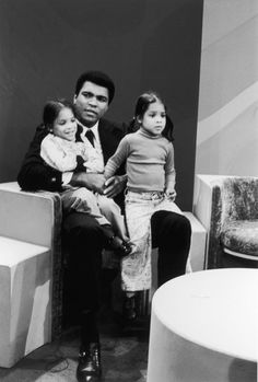 Boxing champ Muhammad Ali affectionately holds his twin daughters,Jamillah and Rasheda, prior to a TV interview with Howard Cosell in 1974.