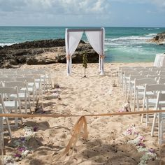 An Intimate Beachfront Destination Wedding in Kahuku, Hawaii = The ceremony was held on the sandy beach at the Turtle Bay Resort with breathtaking views of the Pacific Ocean. Bright pink and white orchids decorating the sparkling sands led to an airy fabric-draped wedding arch.