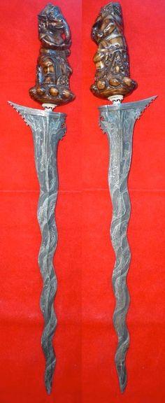 Keris (Bali)  Dapur (style)  Tangguh (era): 20th century  Pamor (surface pattern): Sampir  Blade Features: A kembang kacang is found.   Hulu (hilt): Elaborate elephant carving in Bali style  Mendak (fittings): silver colored