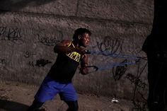 Popole Misenga, a refugee from the Democratic Republic of Congo and a judo athlete, trains using an elastic belt near his home in a slum in Rio de Janeiro, Brazil, June 2, 2016. REUTERS/Pilar Olivares