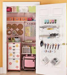 Do not love the pink ... but Craft Room Closet: Supplies tuck away easily within this hidden crafting corner. Pegboard mounted to the door provides ample storage while rolling containers make the space easily accessible.
