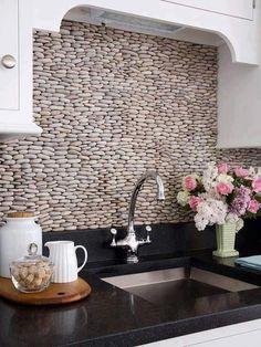 Sabe aquelas pedrinhas comuns de jardim? Olhem só que graça uma parede revestida delas. :)