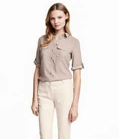 Gently fitted blouse in airy, woven fabric. Buttons at front, chest pockets with flap, and 3/4-length sleeves with roll-up tab and metal buckle.