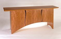 An asymmetrical sideboard made from cherrywood with shaped katalox handle. inside there are two cutlery drawers and secret drawer.