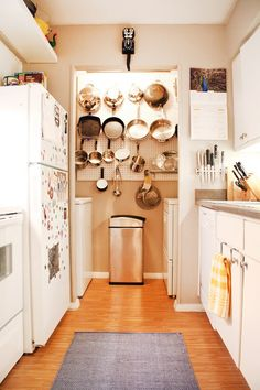 attached all their pots and pans to pegboard they installed to their kitchen wall. This eliminates the need for the cabinet space for these items by using the vertical space available.