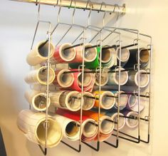Organizing craft vinyl rolls with pants hangers.