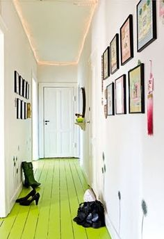 Pasillo decorado con cuadros y suelo color verde.