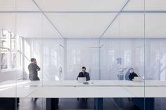 Logan Offices Mesa de 20m de comprimento, dividida por paredes de vidro.