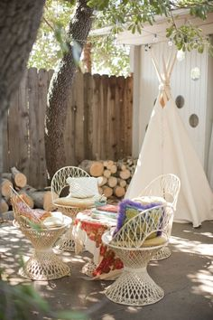 eclectic outdoor sitting area. Love the fun fabrics and the tee-pee.