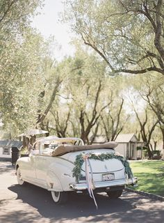 Vintage car decorated with swag of greenery for bride and groom exit. See more French inspired #wedding decor here: http://www.mywedding.com/articles/french-wedding-decor-details/