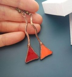 Stained glass and copper wire earrings. The earrings bent copper wire and soldered. At the end of the copper wire there are crazy triangles. I used : -orange stained glass -red stained glass -copper wire -copper foil -solder The length of earrings 2,8 incg - 7 cm There are similar products - https://www.etsy.com/listing/535223934/stained-glass-earrings-art-jewelry - https://www.etsy.com/listing/104454686/stained-glass-jewelry-unusual-earrings...